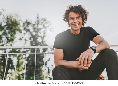 Low view shot of happy stylish young man wears black t-shirt and wirstwatch on the street. Happy smiling man posing for advertisement with copy space, outdoor in the city street. People concept