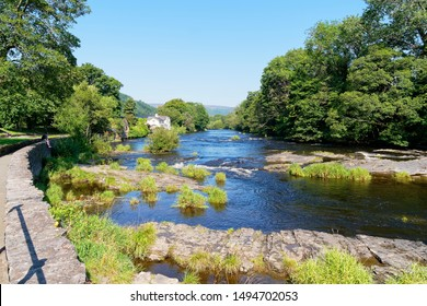A low wall follows the curve of the fast flowing River Dee on a bright summer day in Llangollen, Wales