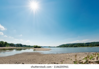 Low water level in the dried-out riverbed of the river Rhine between groins on a sunny day, caused by prolonged drought, North Rhine-Westphalia, Germany, Europe