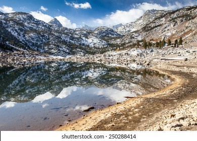 Low water level in a mountain lake reflecting snowy peaks.