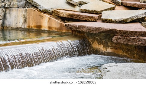 A low waterfall with broken stone slabs on the edge of the canal.