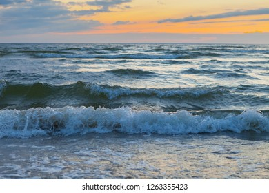 Low waves on Baltic sea at sunset. Cosy flat sandy beach.