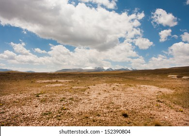 Low white clouds floating over dry land of the mountain plateau in Central Asia