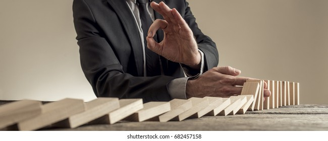 Low wide angle view of man in business clothes stopping dominoes row from crumbling and showing Ok gesture.