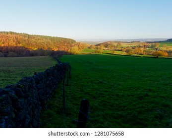 The low winter sun creates deep shadows across the fields and meadows of Derbyshire