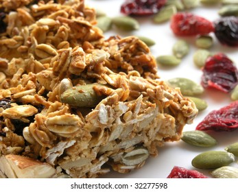 low-angle macro shot of a breakfast granola bar on a white plate sprinkled with pumpkin seeds and dried cranberries
