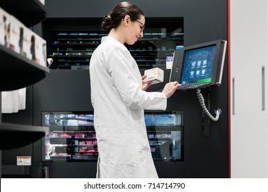 Low-angle rear view of an experienced female pharmacist using a computer while managing the drug stock in a contemporary pharmacy with modern technology