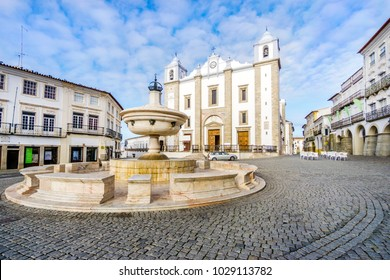 Low-angle shot of a fountain surrounded by traditional residential building and with Saint Anton's Church in the background, Giraldo Square, Evora, Alentejo, Portugal