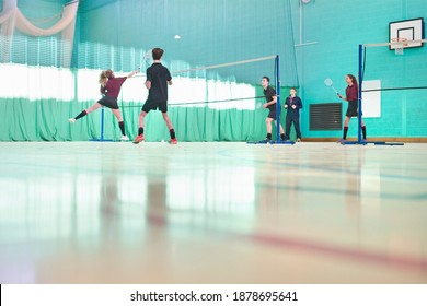 Low-angle shot of high school students playing badminton during a gym class.