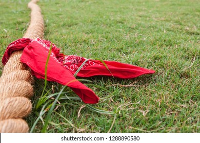 Low-angle shot of thick rope with bandana attached lying on grass field before tug of war game begins.