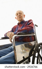 Low-angle view of Caucasion elderly man sitting in wheelchair looking down at viewer.