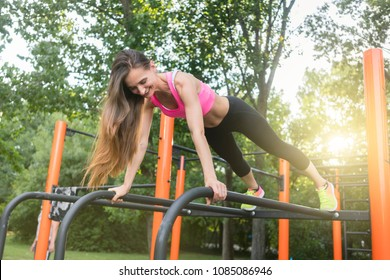 Low-angle view of a cheerful beautiful woman passionate about calisthenics training exercising basic plank position outdoors in a modern fitness park