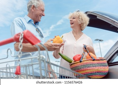 Low-angle view of a cheerful senior couple with a healthy lifestyle happy for buying fresh and nutritious vegetables from the hypermarket