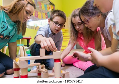 Low-angle view of a dedicated kindergarten teacher helping children with the construction of a wooden train circuit during supervised free playtime