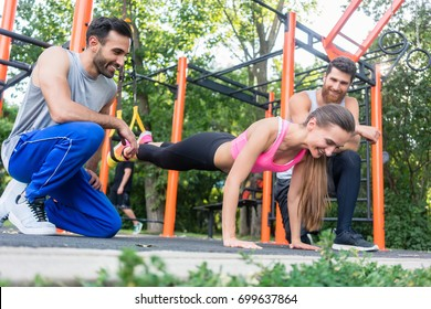 Low-angle view of a fit young woman doing leg extension exercise, with suspension trainer motivated by her cheerful athletic friends in a modern calisthenics park