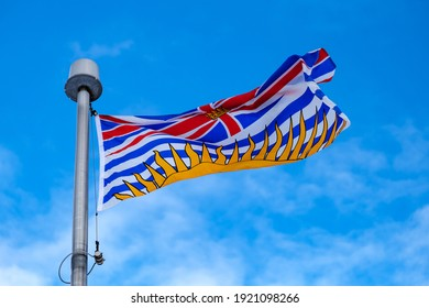 Low-angle view of the flag of the Canadian province of British Columbia (BC) on a flagpole.