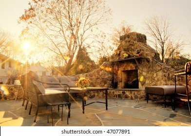Low-angle view of a flagstone patio with an outdoor stone fireplace and furniture. Rays of sunlight stream down. Horizontal format.