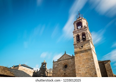 Low-angle view of the main tower of Santa Maria del Azogue roman church in Puebla de Sanabria against a cloudy blue sky, Spain, built in gothic style in the XXII century. Long exposure.