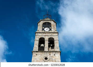 Low-angle view of the main tower of Santa Maria del Azogue roman church in Puebla de Sanabria against a cloudy blue sky, Spain, built in gothic style in the XXII century.