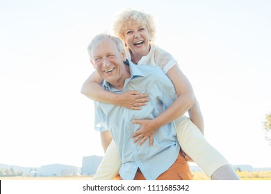 Low-angle view portrait of a happy senior man laughing, while carrying his partner on his back in a sunny day of summer in the countryside