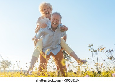 Low-angle view portrait of a happy senior man laughing while carrying his partner on his back, in a sunny day of summer in the countryside