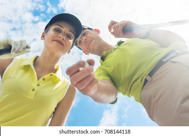 Low-angle view portrait of a young woman smiling while looking at camera during professional golf game with her partner or instructor outdoors