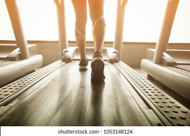 Low-angle view of woman running on treadmill before hard workout.