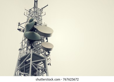 Low-angle vintage shot transmitters and aerials on telecommunication tower with dramatic cloudy sky, digital communication and encryption safety concept