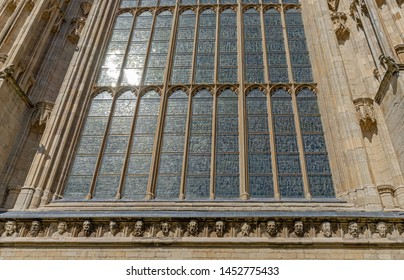 A low-angled view of the East end of York Minster with the medieval stained glassed Great East Window and carvings of historical figures.