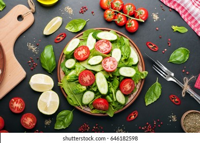 Low-calorie dietary vegan salad plate on a dark background. Salad from spinach leaves, cherry tomatoes and cucumber slices. Useful dietary dinner. View from above
