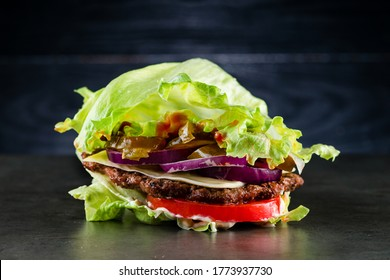 low-carb Burger with salad and beef, Homemade bunless all beef lean hamburger lettuce wrap which is a low carb alternative for those on paleo diet, and topped with tomatoes and onion