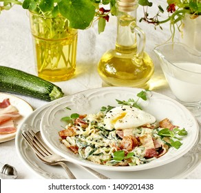 Low-Carb keto carbonara pasta with spaghetti (noodles) of zucchini with cream, fried bacon and poached egg. decorated with pea sprouts. in a beautiful light dish. recipes for fatty protein foods