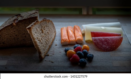 A low-carb , protein-rich meal consisting of swiss cheese, salami; berries, fake fish  and rye bread on wooden plate by a window
