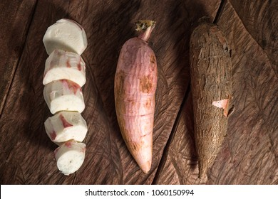 low-cyanide content whole, peeled and cut cassava roots on rustic background