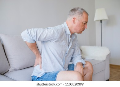 Lower back pain. Man holding his back in pain. Medical concept. Close up hands touching back pain. A man problem chronic low back pain