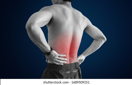 Lower back pain. Shirtless man touching his back with red highlight