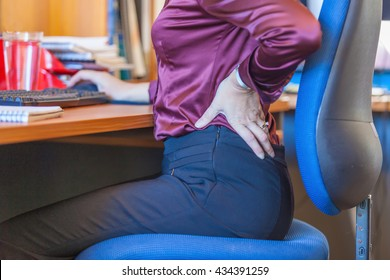Lower back pain from sitting down too long at a desk. A Business woman suffers from  back pain. She is wearing a purple silk shirt top and grey pants.