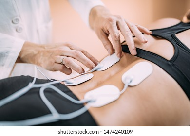 Lower Back Physical Therapy with TENS Electrode Pads, Transcutaneous Electrical Nerve Stimulation. Therapist Positioning Electrodes onto Patient's Lower Back