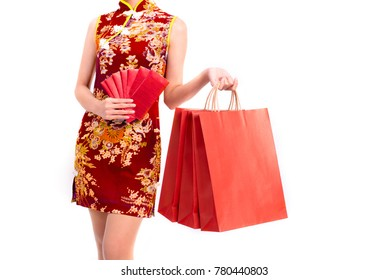 Lower body of Asian beauty woman wearing cheongsam and carry red packet of money and shopping bag in Chinese new year festival event on isolated white background. Holiday and Lifestyle concept. Qipao