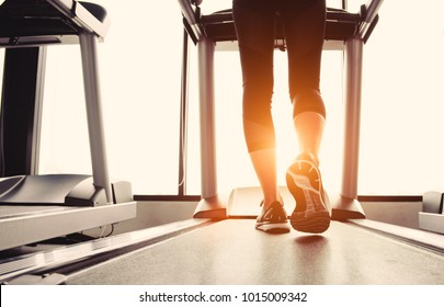 Lower body at legs part of Fitness girl running on running machine or treadmill in fitness gym with sun ray. Warm tone. Healthy and Exercise activity concept. Workout and  Strength training theme.