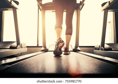 Lower body at legs part of Fitness girl running on running machine or treadmill in fitness gym. Healthy and Exercise activity concept. Workout and  Strength training theme. Closeup