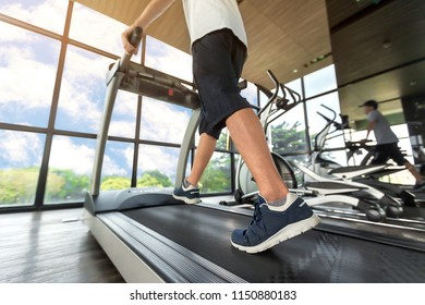 Lower body at legs part of Young man in sportswear running on treadmill machine at fitness gym with sun ray. Warm tone. Healthy and Exercise activity concept. Workout and Strength training theme.