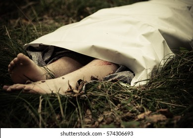 Lower body of murder victim lying outdoors under sheet with bare feet