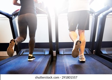 Lower Body Shot of Healthy Athletic Couple Running on Treadmill Machine Inside the Fitness Gym