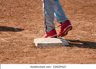 Lower body shot of a teen baseball player standing on base.