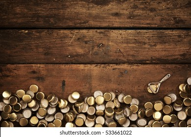 Lower border of old used bottle tops with a small opener over vintage grungy wooden boards in a rustic bar or pub with copy space