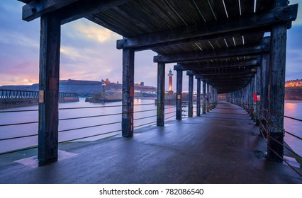 The lower deck of Whitby west pier looking towards Whitby Abbey and Church of Saint Mary, North Yorkshire, England