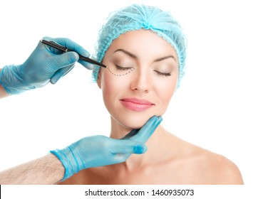 Lower eyelid Plastic surgery concept. Doctor Hands drawing marks on female face isolated on white background. Facial Treatment. Portrait Of Beautiful Sexy Woman Black Surgical Lines around eyes skin