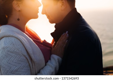 the lower half of the face of the girl and the guy in front of her. sun rays shine on them
