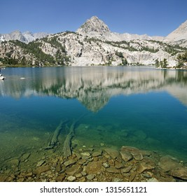 Lower Lamarck Lake with reflection of Sierra mountain and rocks and logs underwater